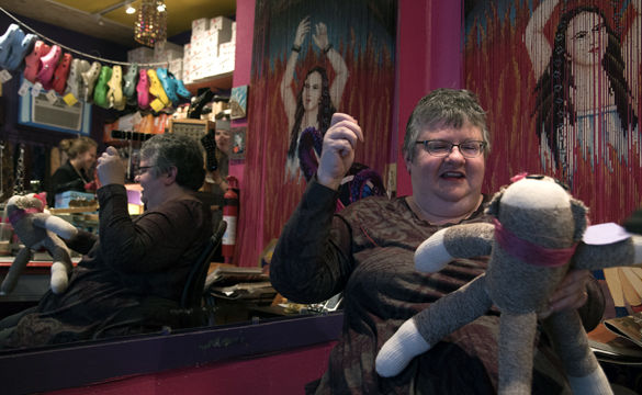 Kim Treger sews a red felt heart onto a sock monkey while chatting with customers Feb. 6 at Walk the Line on the Strip.
