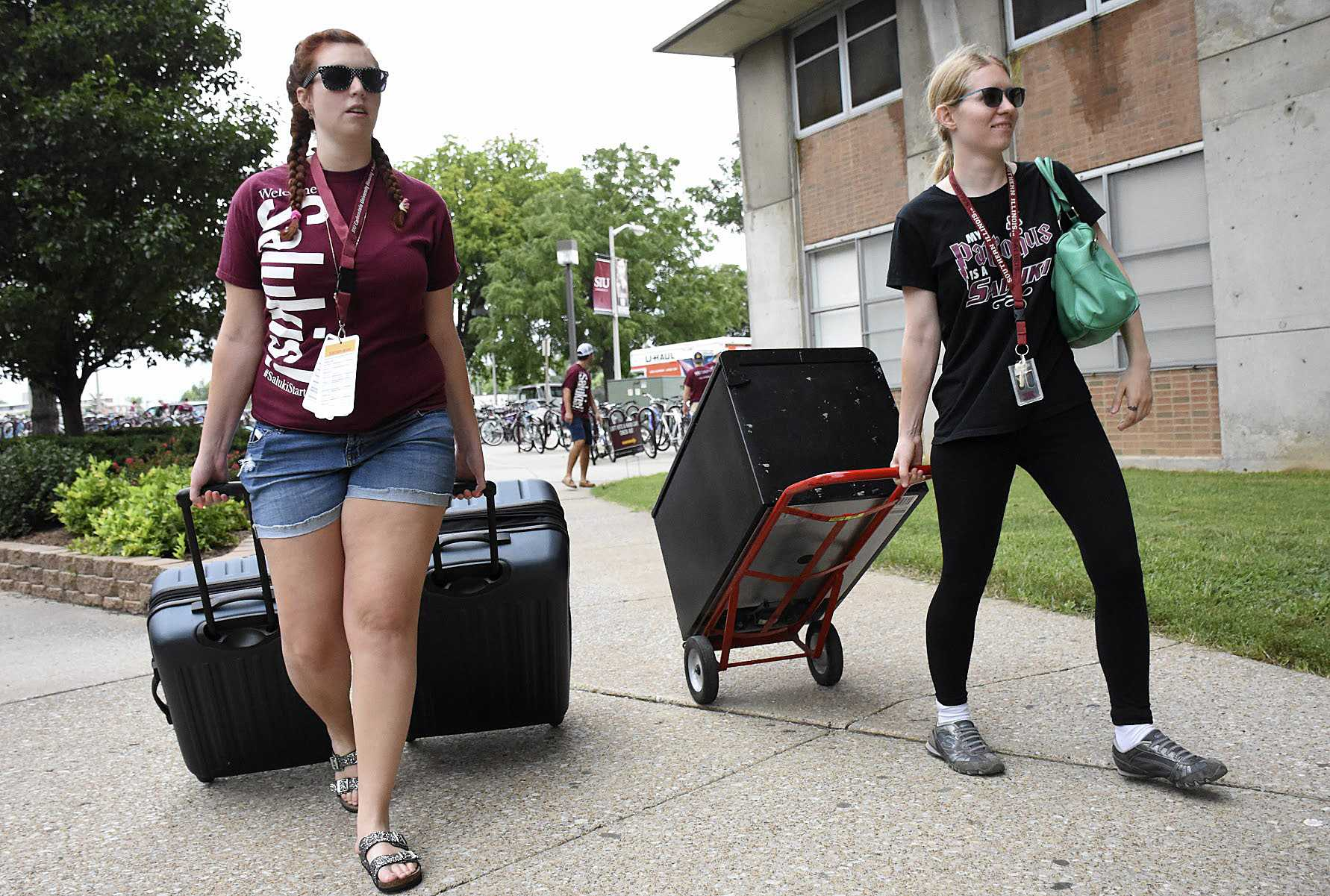 Emmalie Hall, a junior from Chicago studying interior design, moves her belongings with the help of volunteer Desiree Smith on Friday outside Mae Smith Hall. (Athena Chrysanthou | @Chrysant1Athena)