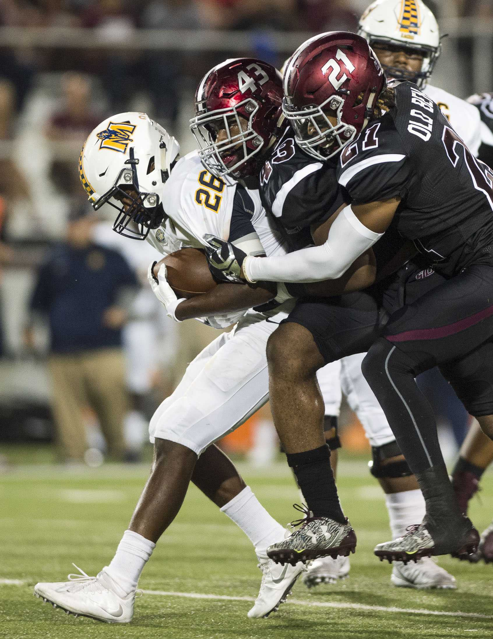 SIU senior defensive end Deondre Barnett (43) and junior safety Ryan Neal (21) work to stop Racer junior running back Demetric Johnson (26) during the Salukis' 50-17 win over the Murray State on Saturday, Sept. 17, 2016, at Saluki Stadium. (Ryan Michalesko | @photosbylesko)