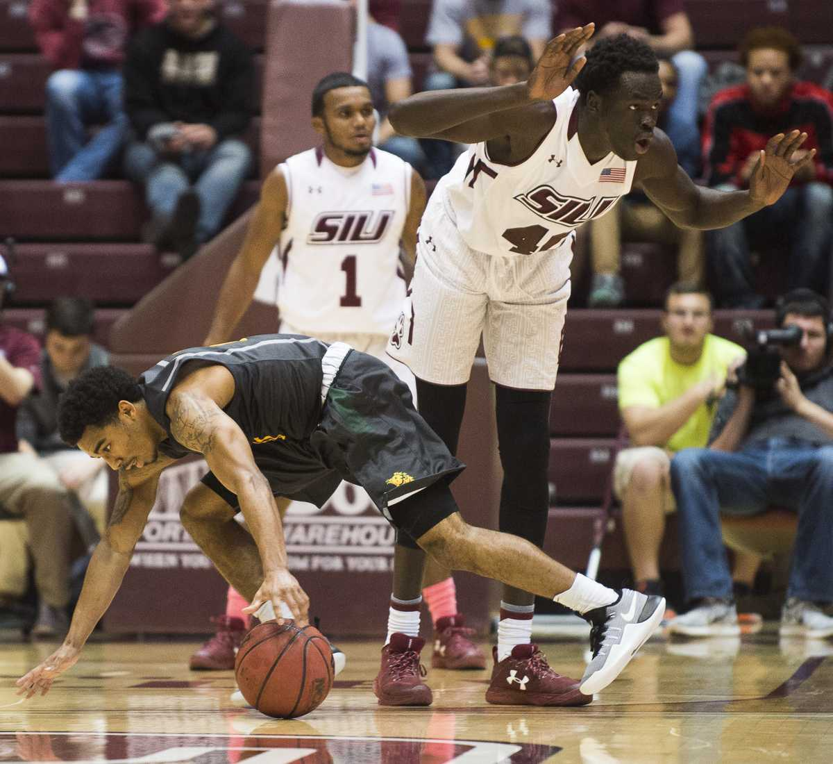 Junior forward Thik Bol (40) holds himself back from fouling as Missouri Southern junior guard CJ Carr (0) attempts to recover a loose ball Wednesday, Nov. 16, 2016, during the Salukis' 85-64 win over the Missouri Southern Lions at SIU Arena. (Ryan Michalesko | @photosbylesko)