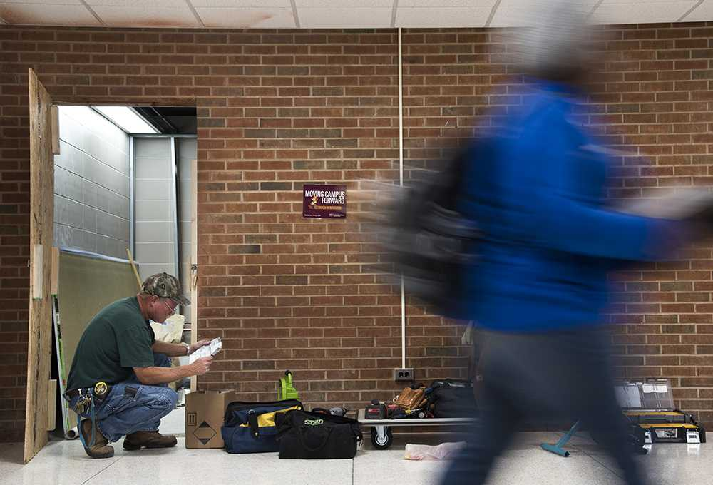 Construction worker Tom Clark, of Carterville, reads notes Tuesday, Nov. 29, 2016, while remodeling the plumbing and lights in the new gender-neutral bathrooms in Trueblood Hall.  (Morgan Timms | @morgan_timms)