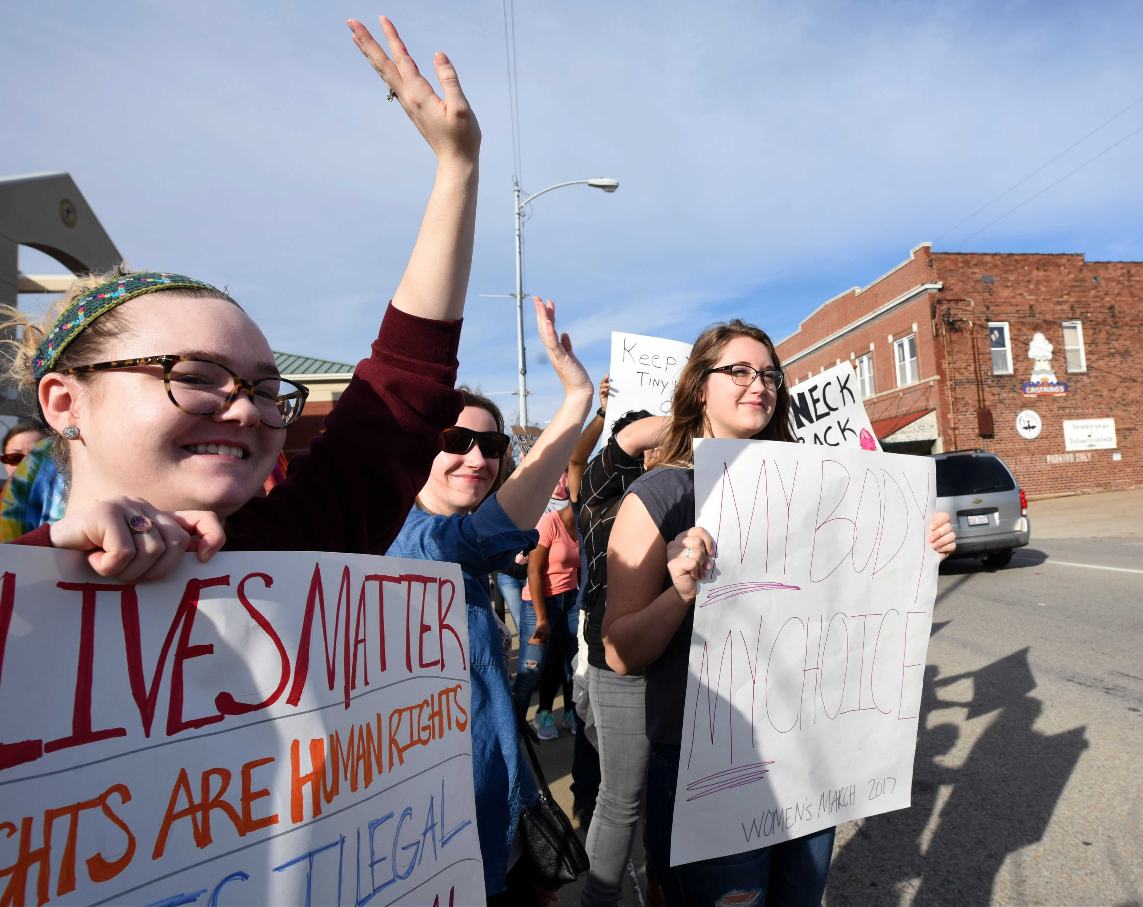 Demonstrators participating in the Southern Illinois Women's March wave to passing cars on Saturday, Jan. 21, 2017, in front of the Carbondale Civic Center. (Bill Lukitsch | @lukitsbill)