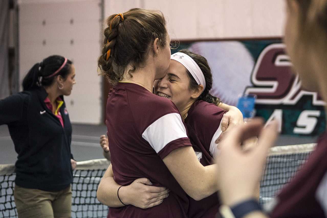 From left: senior Meagan Monaghan congratulates junior Vitoria Beirao on Friday, Feb. 24, 2017, after her singles win in straight sets against Southeast Missouri State sophomore Ana Canahuate-Torres at Garden Grove Event Center in Carbondale. (Athena Chrysanthou | @Chrysant1Athena)
