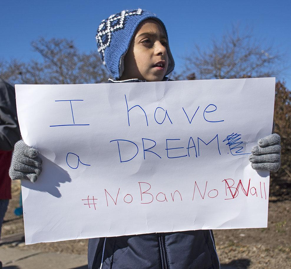"Alihadi Srour, 8, of Carbondale, holds a sign during the Peace Coalition of Southern Illinois monthly vigil Saturday, Feb. 4, 2017, on East Main Street. Srour was born in the United States and his mother, Nour Srour, was born in Lebanon. Nour believes President Donald Trump uses language that separates people based on their religion instead of uniting them. ""I witnessed four wars when I was growing up and I don't want my kids to see that horror in their life, no matter where they are living,"" Nour said. ""I don't want them to grow up and feel scared to show who they are or where they are from."" (Athena Chrysanthou 