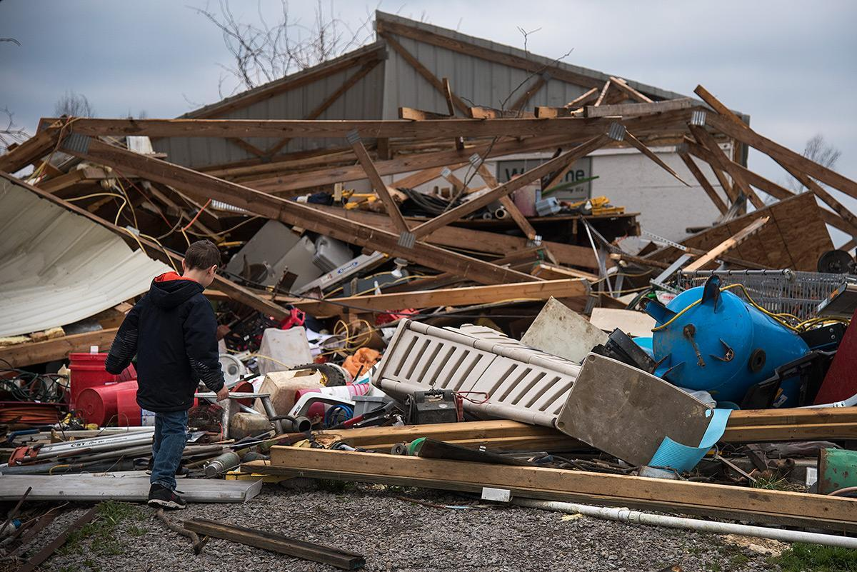 """Seven-year-old Mayson Robinson, of Willisville, traverses the wreckage of his aunt Kassi Coulson's barn Wednesday, March 1, 2017, in Ava. Tuesday night a tornado damaged the roof of Coulson's home, from which daylight can now be seen from inside the house, destroyed the family's barn, knocked down trees and damaged vehicles. """"You just don't think it's going to hit you like that,"""" Coulson said. """"All in like a blink of an eye just the wind was in here, my five-year-old's crying and screaming. … When I was shutting that door I could literally feel the air in here. I thought that window was open, I didn't realize it was the roof."""" (Jacob Wiegand 