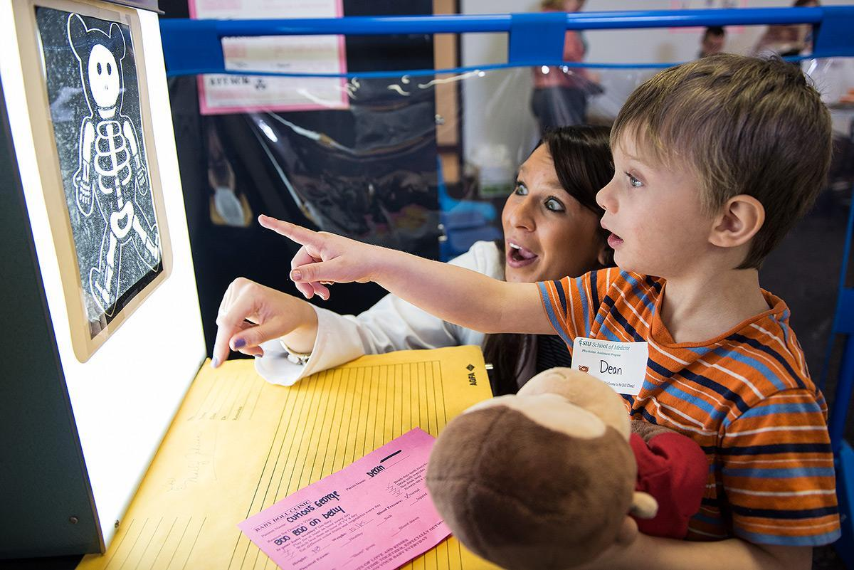 "Dean, a student in SIU's Head Start program, and Alexandra Spillman, a student in the physician assistant program from Effingham, look at an X-ray of Curious George during a doll clinic March 8, 2017, at the Head Start center in Carbondale. Adam Guss, a student in the physician assistant program from Milan, said the kids pretend their dolls are their own children when they come to the clinic. ""It just brings kids to light about making them more comfortable coming into the doctor's office,"" Guss said. ""Seeing their dolls, or babies as we call them, be more comfortable then it makes them more comfortable coming into see us."" This is the fifth year for the doll clinic. Head Start requested the last names, hometowns and ages of children not be published. (Jacob Wiegand 