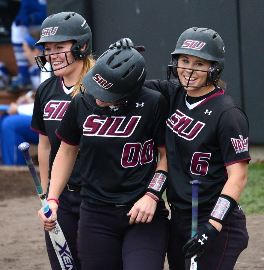 Senior+catcher+Jessa+Thomas%2C+left%2C+junior+third+baseman+Sydney+Jones+and+junior+shortstop+Savannah+Fisher+and+celebrate+scoring+Sunday%2C+March+26%2C+2017%2C+in+the+fourth+inning+of+SIU%27s+6-2+victory+against+Drake+in+the+first+game+of+its+doubleheader+at+Charlotte+West+Stadium.+%28Sean+Carley+%7C+%40SeanMCarley%29