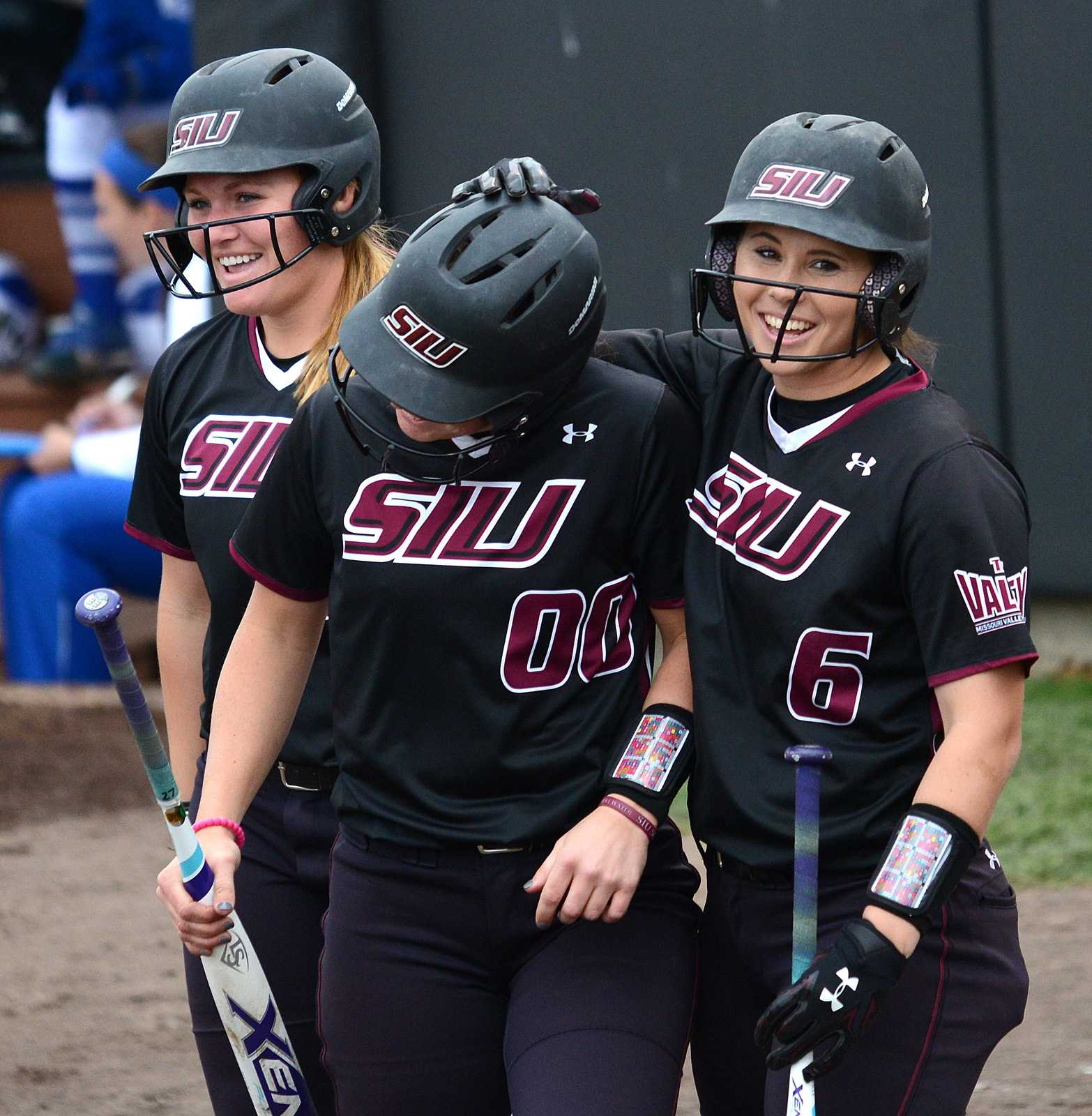 Senior catcher Jessa Thomas, left, junior third baseman Sydney Jones and junior shortstop Savannah Fisher and celebrate scoring Sunday, March 26, 2017, in the fourth inning of SIU's 6-2 victory against Drake in the first game of its doubleheader at Charlotte West Stadium. (Sean Carley | @SeanMCarley)