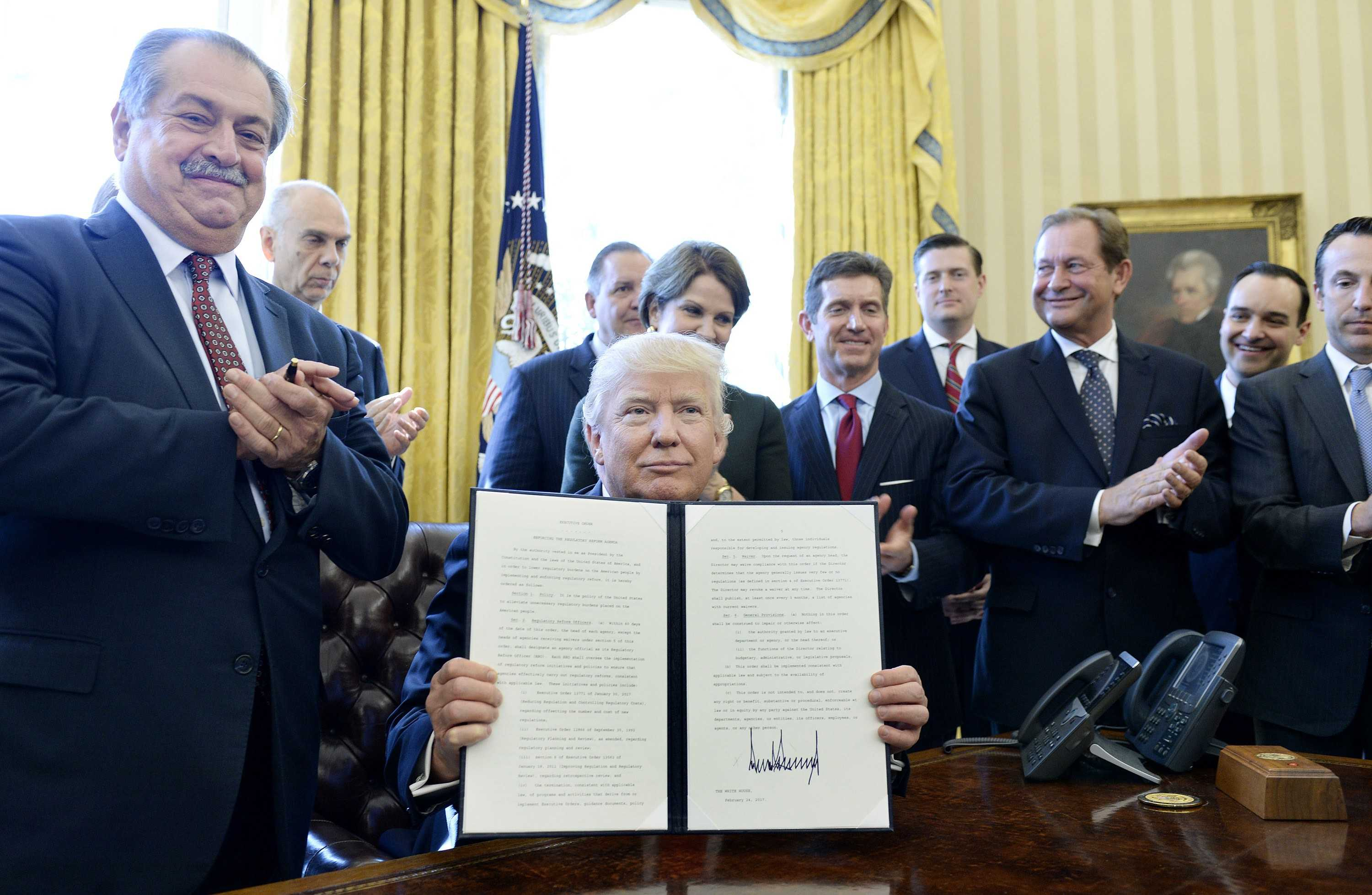 U.S. President Donald Trump, flanked by business leaders, signs an executive order establishing regulatory reform officers and task forces in US agencies in the Oval Office of the White House on Feb. 24, 2017 in Washington, D.C. (Olivier Douliery | Abaca Press)