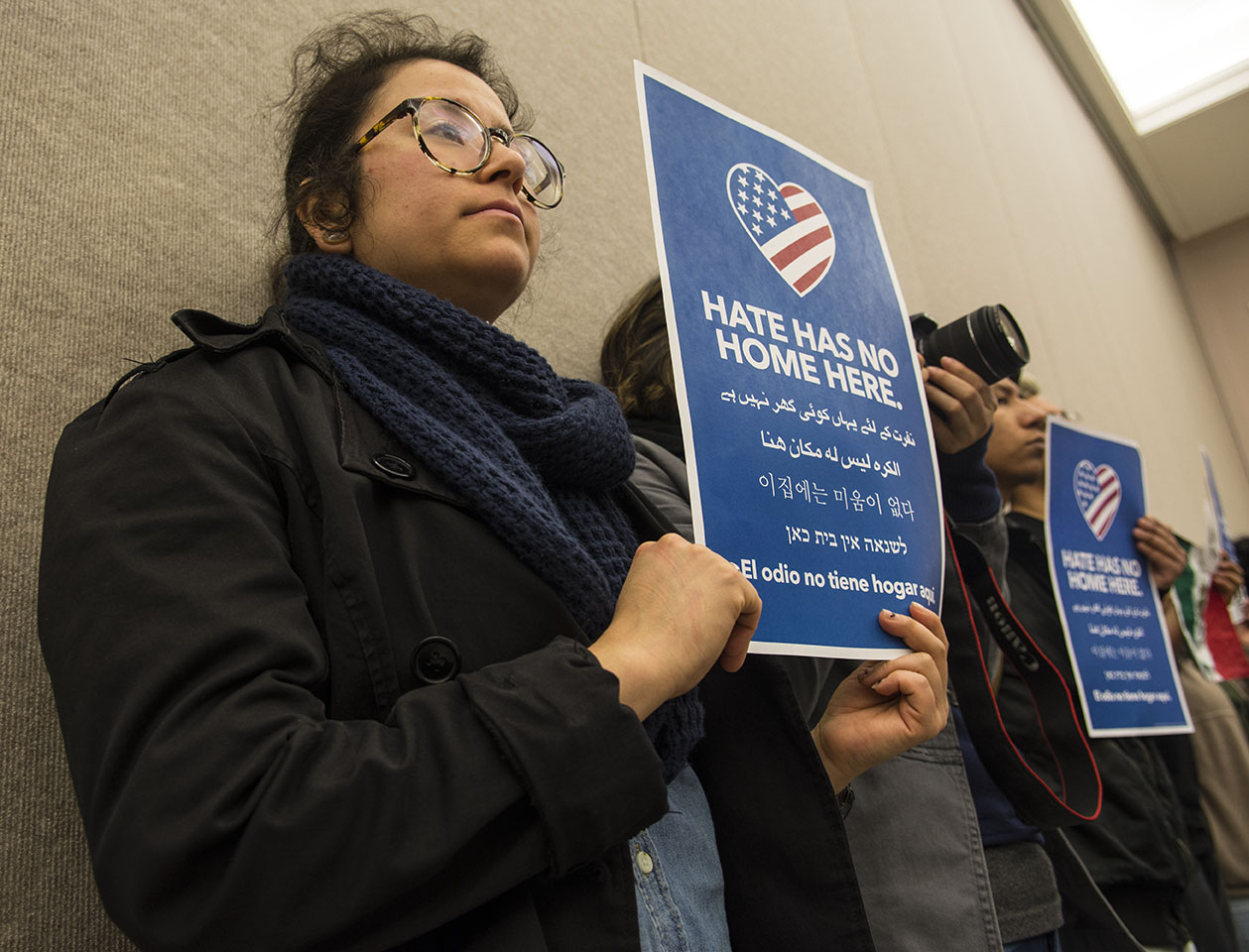 "Martha Osornio, a senior from Chicago studying cinema and photography, holds a ""Hate has no home here."" sign Tuesday, April 11, 2017, during a city council meeting at the Carbondale Civic Center. Osornio, whose family immigrated illegally to the United States in 1992, attended the meeting with five other students from the Hispanic Student Council to support the resolution establishing Carbondale as a safe and welcoming community. Osornio said she has friends in Chicago who fear they might be deported for insignificant issues if they enrolled at SIU."