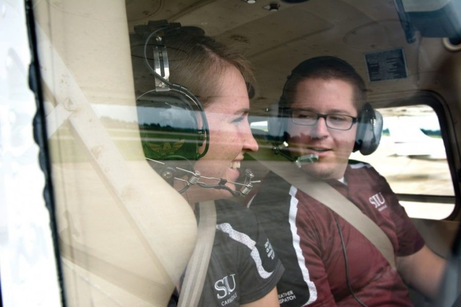Sarah Demkovich, a senior from Algonquin studying aviation management, laughs with Michael Bacha, a graduate student from Palatine studying public administration, during a pre-flight inspection Aug. 18, 2014, at the Southern Illinois Airport. (DailyEgyptian.com file photo)