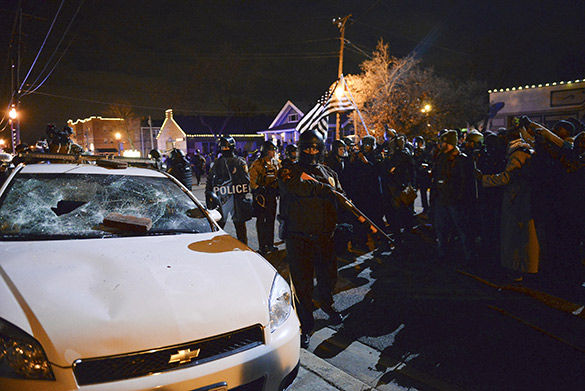 Police push protesters back after people broke the windows of a St. Louis County Police vehicle Nov. 25, 2014 in Ferguson, Mo. -Nathan Hoefert
