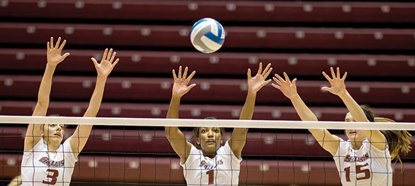 Sophomore Meg Viggars, left, junior Taylor Pippen, center and freshman Abby Barrow jump to block a ball Dec. 9, 2014, during the Saluki Invitational at Saluki Stadium. (DailyEgyptian.com file photo)