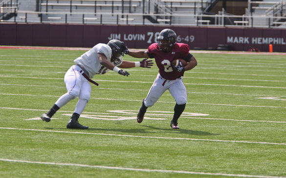 Then-junior running back Aaron Stanton makes a block as he runs with the ball on April 14, 2015, during an SIU scrimmage. (DailyEgyptian.com file photo)