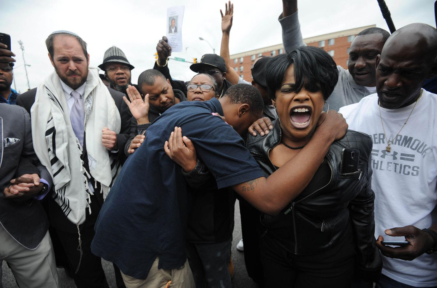 Rev. Pamela Coleman, right, prays with Baltimore residents at the corner of West North Avenue and Pennsylvania Avenue on May 1 after charges were filed against six Baltimore police officers in the death of Freddie Gray in Baltimore, Md. (Kim Hairston/Baltimore Sun/TNS)