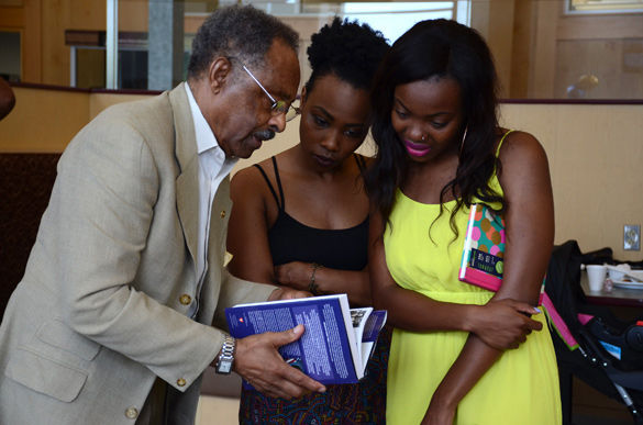 "Former Sen. Roland Burris shows his book on July 22, 2015, to Kia Smith, right, a junior from Chicago studying journalism, and Rashionda Carlisle, a senior from Belleville studying social work. Burris said the reason he has passion for SIU is it gave him the tools he needed for his career, but he wants to ensure black students after him have similar opportunities. ""There is racism in our society,"" Burris said. ""There are students living in poverty conditions and we are trying to uplift our whole race of people. Those of us that have been fortunate enough to get a college education to compete in society in spite of racism, we have to make sure that our pipe line is still there."" (Daily Egyptian file photo)"