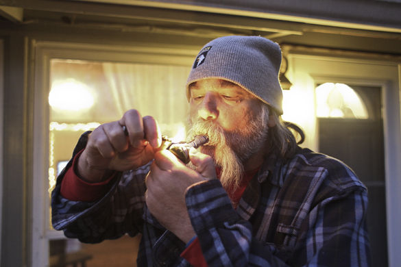 Barry Banks, a graduate student in curriculum and instruction, smokes medical marijuana from a glass pipe Saturday, Nov. 21, 2015, at his home. Banks receives the prescription for diabetic neuropathy and is currently participating in a statewide pilot program. Before he received medical marijuana, Banks was prescribed opiates that he believes has harsher side effects.