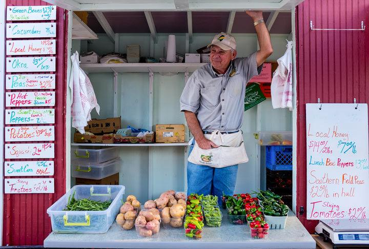 Homer Jenkins, of Murphysboro, smiles in his vegetable stand Wednesday at the Carbondale Community Farmers Market. After graduating from SIU, Jenkins raised hogs until three years ago when he opened his business