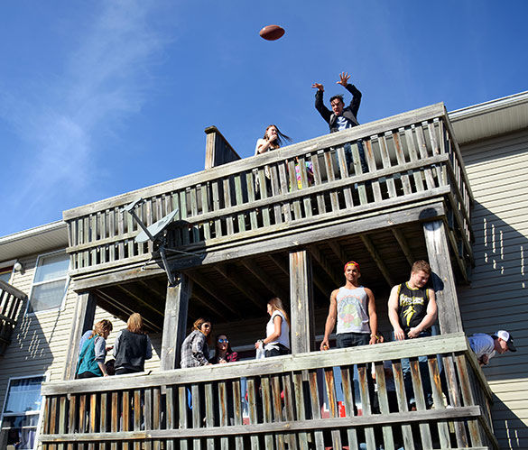 A Polar Bear participant tosses a football from a balcony to partiers below Jan. 30 on South Poplar Street. (DailyEgyptoan.com file photo)