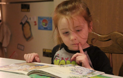 Adalynn Wille, 5, enjoys looking through a book while visiting her grandpa on Jan. 24 at his apartment in Carbondale. Wille attends one of four Head Start Centers and receives new books through SIU Head Start's