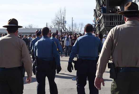 """Members of the Illinois State Police and Carbondale Police Department walk toward partygoers at a Polar Bear event in response to a noise complaint Jan. 30 on South Poplar Street. Carbondale Police Sgt. Doug Wilson said the city had extra officers on duty until 3 a.m. Sunday. """"We're doing alcohol enforcement and trying to prevent people from getting alcohol poisoning,"""" Wilson said.(Jacob Wiegand 