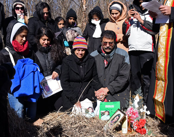 Front row, from left to right: Pravin Varughese's younger sister Preethi, his older sisterPriya, his mother Lovely and his fatherMathew kneel during a memorial ceremony on Saturdayin the woods bordering Illinois Route 13, where police say he died of hypothermia about two years ago.(Luke Nozicka | @lukenozicka)