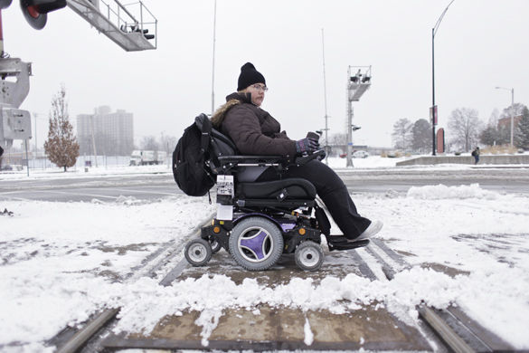 "Sidewalks and snow — transportation barriers wheelchairs users deal with in the winter — don't mix. Carrie Mulderink, a graduate student in communication studies from Chicago, crosses the West Grand Avenue railroad tracks in a motorized wheelchair on her way to class Monday morning. It takes her about 30 minutes to get from her apartment on West Grand Avenue to Morris Library. ""I feel that it's largely unsafe for people with disabilities to cross a railroad that is often uncleared of snow and ice,"" Mulderink said. She said she often gets stuck on the tracks, even if there is no snow. When this happens, Mulderink said she usually has to wait for someone to come find and help her. In the past, she said people have approached her thinking her wheelchair on the tracks was a suicide attempt, so now when she can't get her chair over the tracks, she has to yell for help. Each time she leaves her apartment, Mulderink said she has to consider the safety and potential consequences of traveling to and on campus. Last year, she said she missed about a week of classes because of winter weather conditions. However, she said her teachers are typically accommodating of her situation. ""I'm always trying to give more attention to accessibility issues,"" Mulderink said. ""It's something that should be talked about more. But it isn't."" - Feb. 15, 2016, Carbondale, Ill."