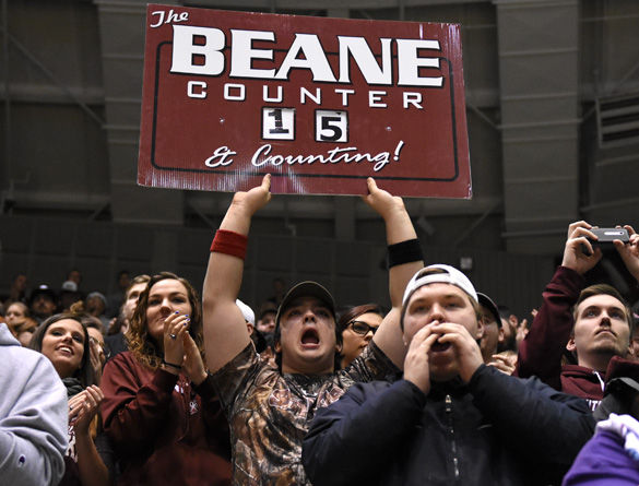 """Patrick Codo, a freshman from Naperville studying sports broadcasting, holds """"The Beane Counter"""" sign while celebrating the news that senior guard Anthony Beane reached 1,000 career points in conference games during SIU's 75-60 win over Drake on Feb. 13 at SIU Arena. """"I had a good feeling he was going to break the record today and guess what, he did,"""" Codo said. """"And I was awesome enough to hold up the sign of numbers he shot, 31 points. And it's also like a great bounce back because we've had the struggles throughout the year, but hey, we managed to get our swagger back and get a win today.""""(Jacob Wiegand 
