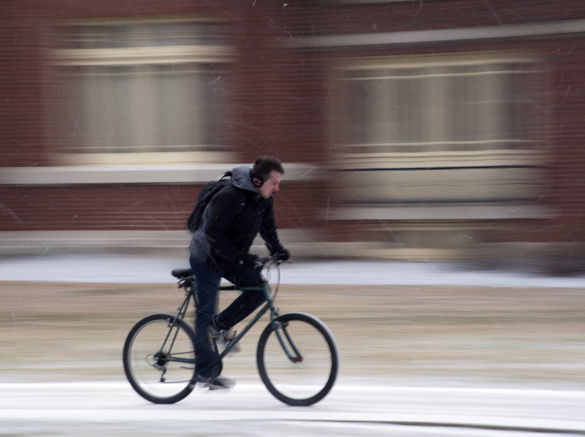 A student braves the snow while biking to class Tuesday outside Faner Hall.