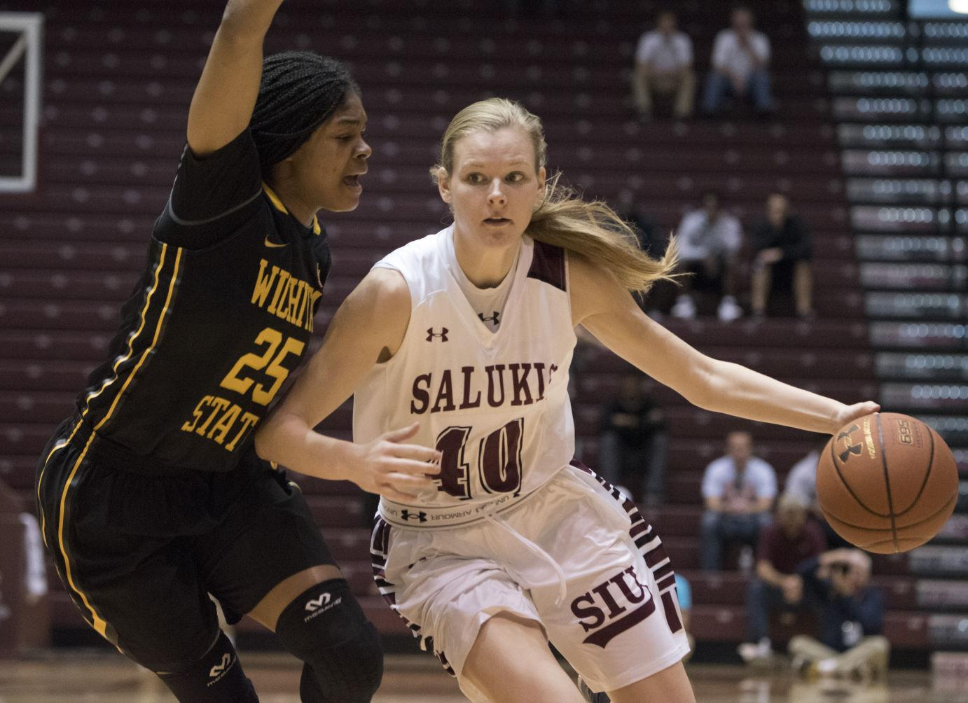 Then-junior guard/forward Carlie Corrigan keeps the ball away from the defense during SIU's victory against the Shockers on Sunday, Feb. 21, 2016 at SIU Arena. Corrigan scored five points with two rebounds and two assists, aiding the Salukis in a 80-66 victory over the Shockers.