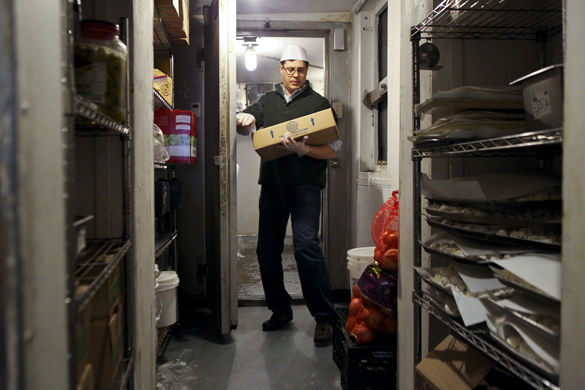 Ethen Jefferson, co-owner of El Greco, carries baklava, a layered dessert, out of a walk-in refrigerator in the back Saturday, Feb. 13, 2016, at the restaurant in Carbondale. (Aidan Osborne | Daily Egyptian)
