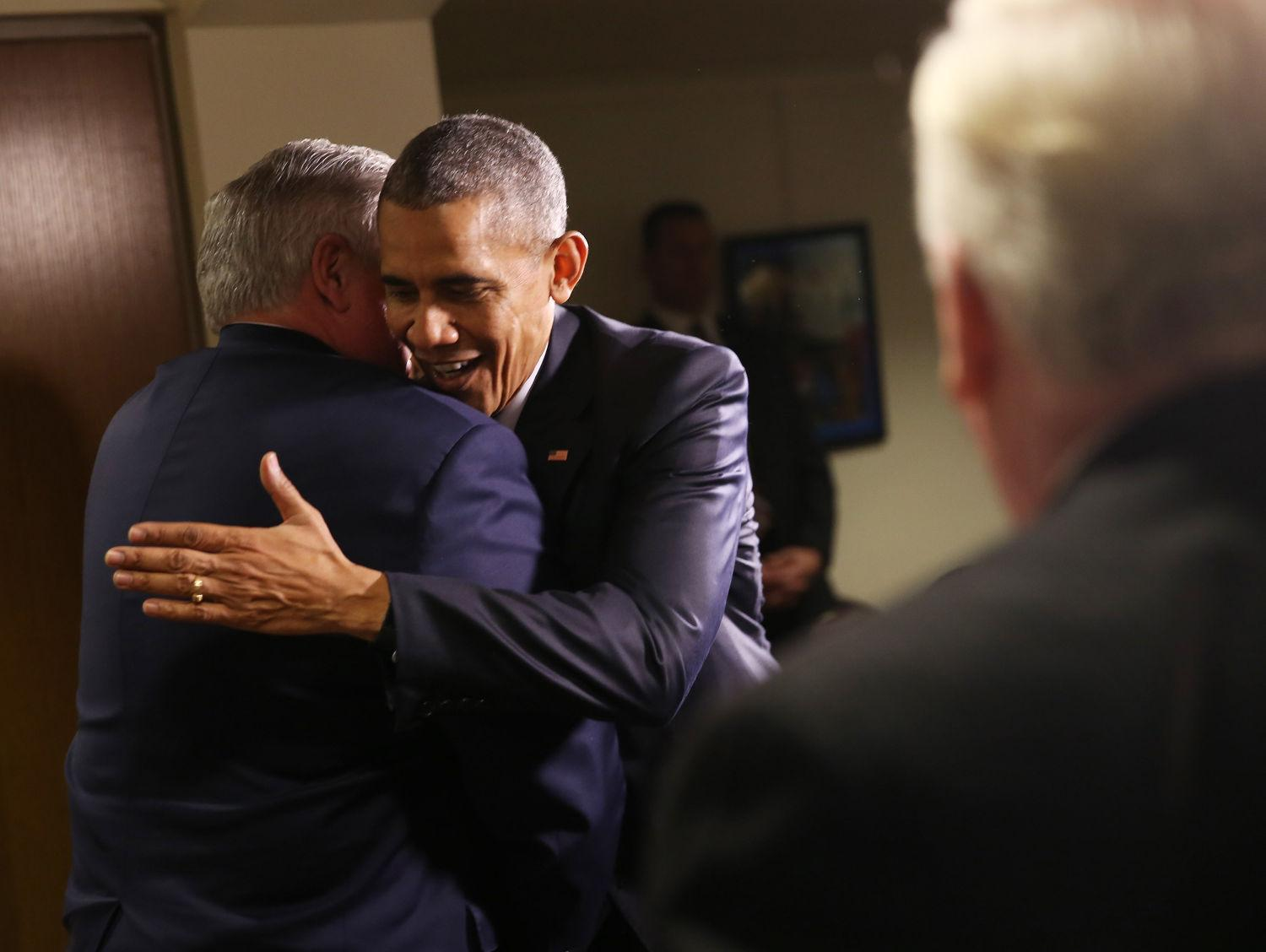 President Obama, center, hugs former Illinois Sen. Kirk Dillard, left, on Feb. 10 in Springfield, before meeting former colleagues from the Illinois General Assembly. They discussed the issue of partisanship in a meeting with Tribune Publications White House Correspondent Christi Parsons, right. (TNS)