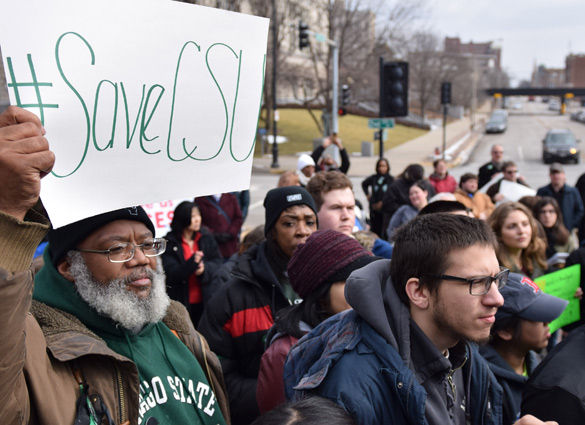 A protestor holds a #SaveCSU sign Feb. 26 at a rally in front of the State Capitol in Springfield. (DailyEgyptian.com file photo)