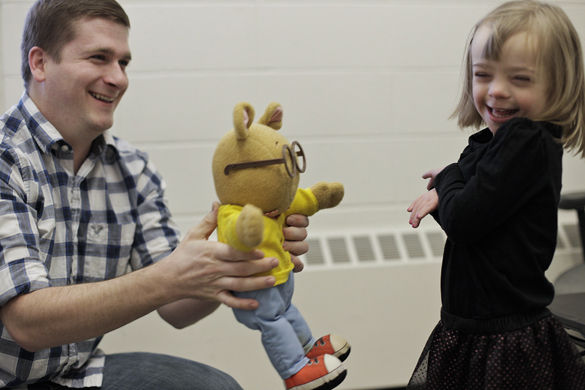 Caleb Stanley, left, a doctoral student in behavior analysis and therapy from Walnut, Miss., offers Faith Teckenbrock, 4, an