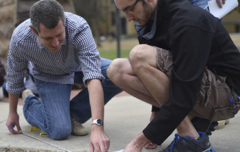 "Nathan Meissner, left, an SIU graduate with his Ph.D. in archaeology, measures ground distance with Chad Hall, a senior from Decatur studying criminology and criminal justice, during an archeological site examination Tuesday at the site of the Old Main building. ""We've done a couple limited tests with [the ground penetrating radar], but this is the largest run,"" said Meissner, a current research associate. ""It's a learning experience for us.  An amazing thing would be to use this equipment full scale at a large prehistoric site here in southern Illinois. I like using high tech equipment, it bring out the inner nerd in me."""