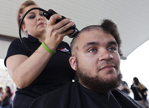 Devin Hunter, a senior from St. Louis studying linguistics, gets his head shaved by Ashley Comerford, an employee at the Sport Clips in Marion, on April 18 during a fundraising event for St. Baldrick's Foundation in the pavilion behind the Student Services Building. Participants in the fundraiser donated money toward childhood cancer research and then shaved their heads. Comerford said this is the first time she has participated in this event and hopes she can again in the future.