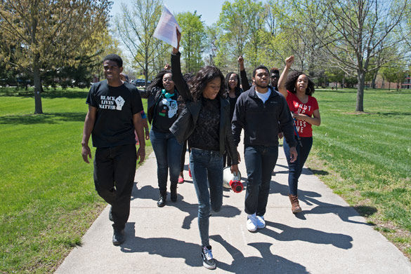 Leilani Bartlett, middle with papers, a freshman from Chicago studying business, leads a march April 12 from Brown Hall to Morris Library. Bartlett, who organized the event, posted a video to Facebook on April 4 expressing her concerns about racism she said she has experienced at SIU. Her video received over 161,000 views. Matthew Wilson, a senior from Carbondale studying TV and digital media radio, participated in the event.