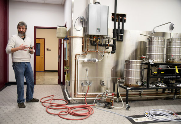"""Matt McCarroll, a fermentation science professor, stands next to a brewing system Jan. 25 in one of McClafferty Annex's new fermentation classrooms. """"Previously we've had to teach our chemistry beer and brewing class spread out in different places,"""" McCarroll said. """"But this is the first time teaching it in a dedicated facility in five years."""" McCarroll said SIU's four-year fermentation science degree is pending with the state and he anticipates its approval in March."""