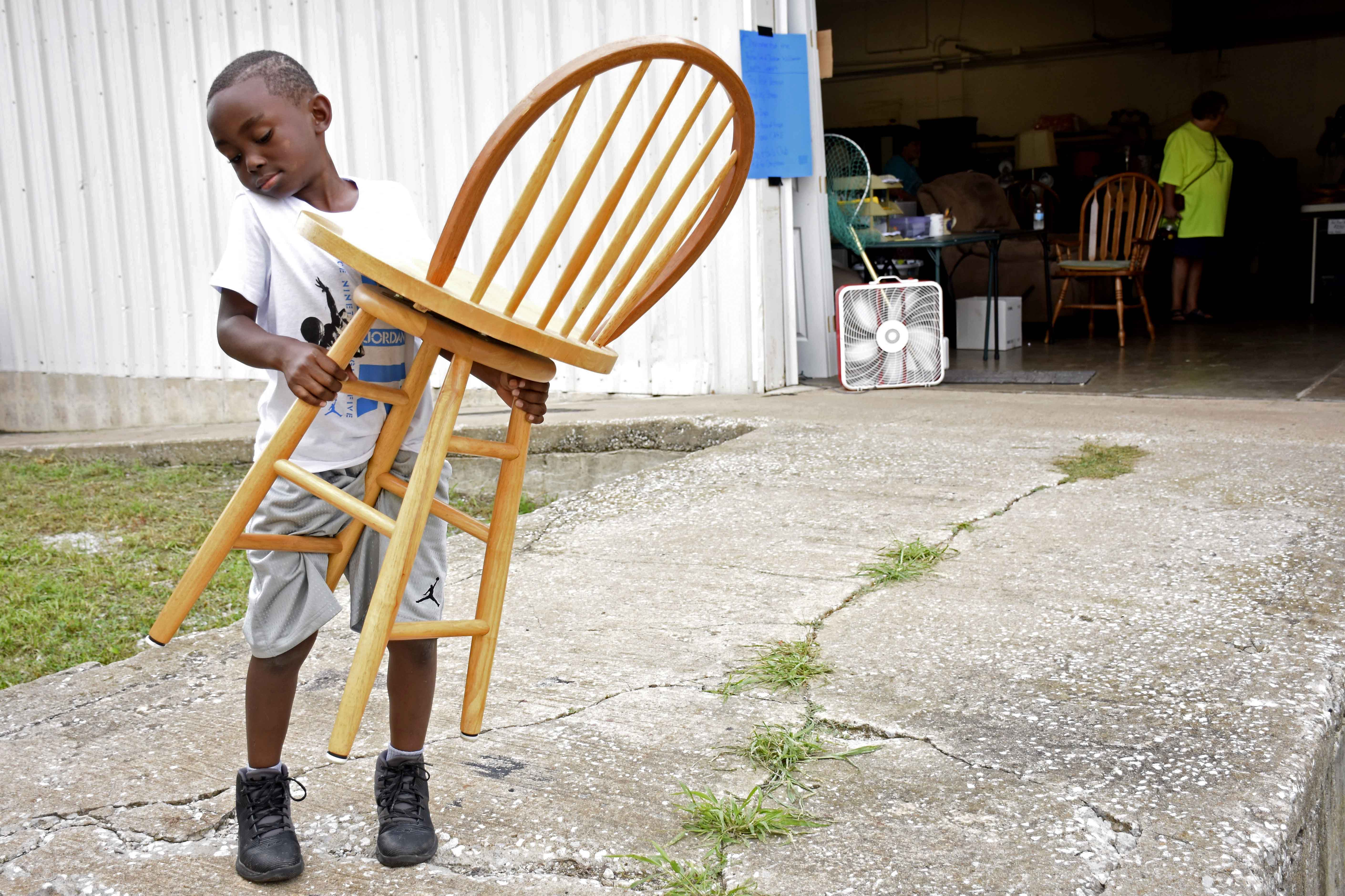 Titan Hills, 6, holds a chair at the Rotary Rotation Resale on Thursday, Aug. 18, 2016, in Carbondale. Hills carried the chair to assist his mother, Tanasha Rodgers. (Athena Chrysanthou | DailyEgyptian.com)