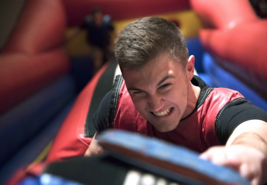 Jake Ellsworth, a sophomore from Evansville, Ind., studying musical theater, reaches for a flag while competing with his friend, Michael Radford, a freshman from Valparaiso, Ind., studying musical theater, on the inflatable bungee run Saturday, Aug. 20, 2016, during Dawgs Nite Out at the Student Center. (Morgan Timms | @morgan_timms)