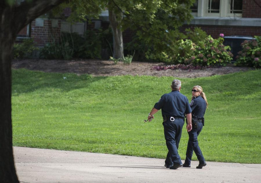 Lt. Ryan House, left, and Officer Molly Pyatt of the SIU Police Department converse as they depart from Shryock Auditorium following a zero-person turnout for the department's rescheduled Pokémon with the Police event Monday, Aug. 22, 2016, in Carbondale.
