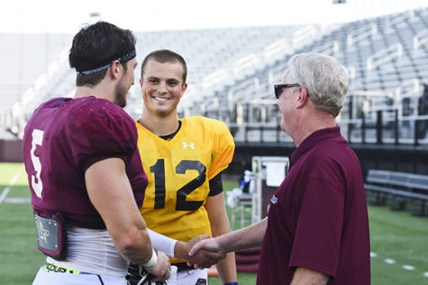 SIU's Director of Broadcast Operations Mike Reis congratulates newly-crowned starting quarterback Josh Straughan alongside senior middle linebacker Chase Allen on Wednesday, Aug. 24, 2016, at Saluki Stadium. (Athena Chrysanthou | @Chrysant1Athena)