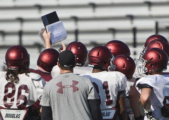 Saluki football players gather around a coach to study a play during practice Wednesday, Aug. 24, 2016, at Saluki Stadium. (Athena Chrysanthou | @Chrysant1Athena)