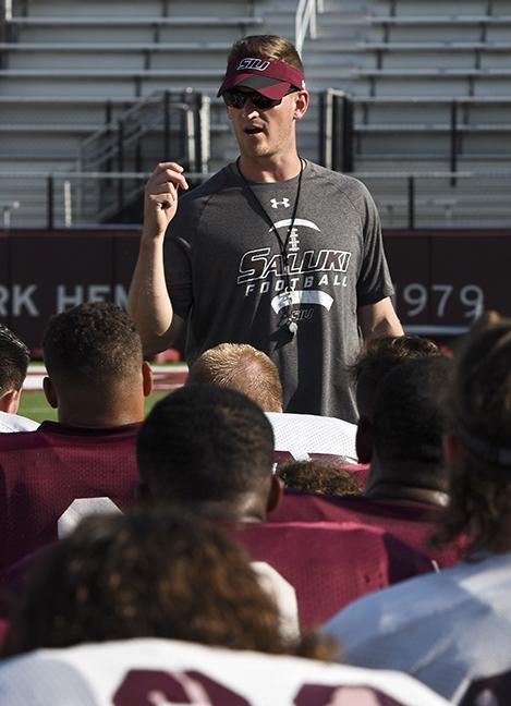 Head football coach Nick Hill debriefs with players after practice on Wednesday, Aug. 24, 2016, at Saluki Stadium. (Athena Chrysanthou | @Chrysant1Athena)
