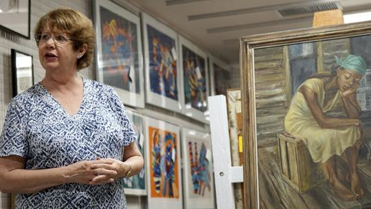 """University Museum director Dona Bachman discusses the restoration of Aaron Bohrod's painting, """"Dreams,"""" on Thursday, Aug. 25, 2016, in the University Museum's archives warehouse. (Andy Phillippe 