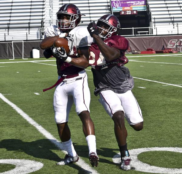 Sophomore wide receiver Jimmy Jones catches a pass alongside sophomore safety Jefferson Vea on Tuesday, Aug. 30, 2016, during practice at Saluki Stadium. (Autumn Suyko | @AutumnSuyko_DE)
