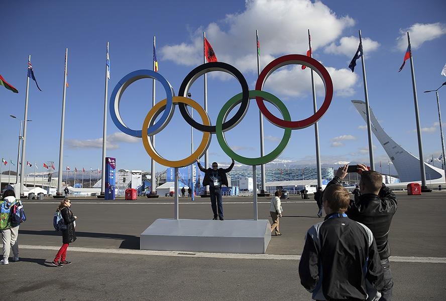 People pose with the Olympic rings inside Olympic Park at the Winter Olympics in Sochi, Russia, Thursday, Feb. 6, 2014. (Brian Cassella/Chicago Tribune/MCT)