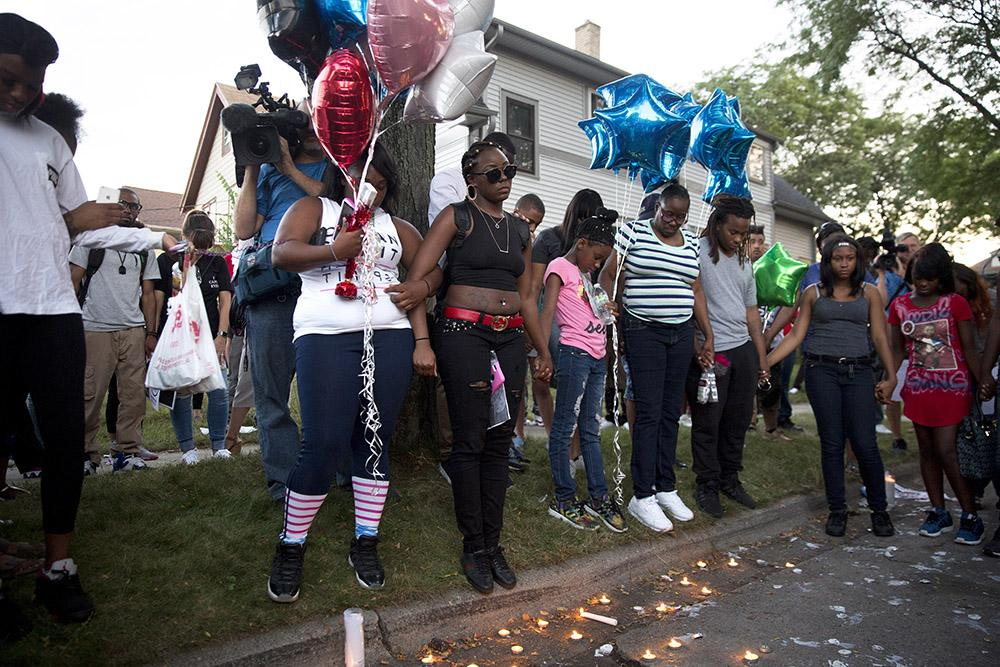 From center, Kimberly O'Neal, the sister of Sylville Smith, who was shot by the Milwaukee police the day before, stands with supporters during a vigil for her brother Sunday in Milwaukee, Wis. (Armando L. Sanchez/Chicago Tribune/TNS)