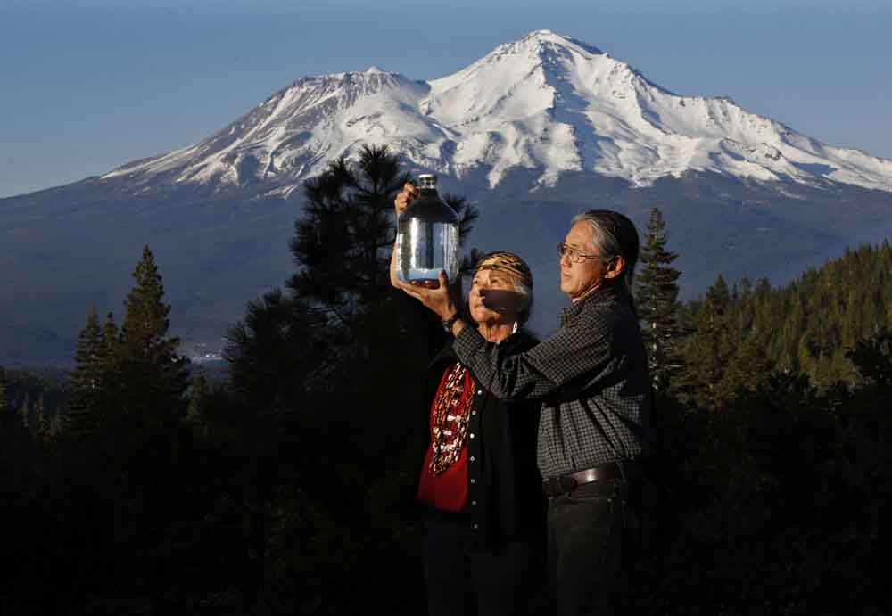 Luisa Navejas, 69, and her husband Mark Miyoshi, 64, hold a bottle of water from their home well on April 16, 2015 at the base of Mount Shasta, Calif. The members of the Winnemem Wintu tribe consider all sources of the pure drinking water to be sacred and the tribe has joined the fight against Crystal Geyser. Navejas said,
