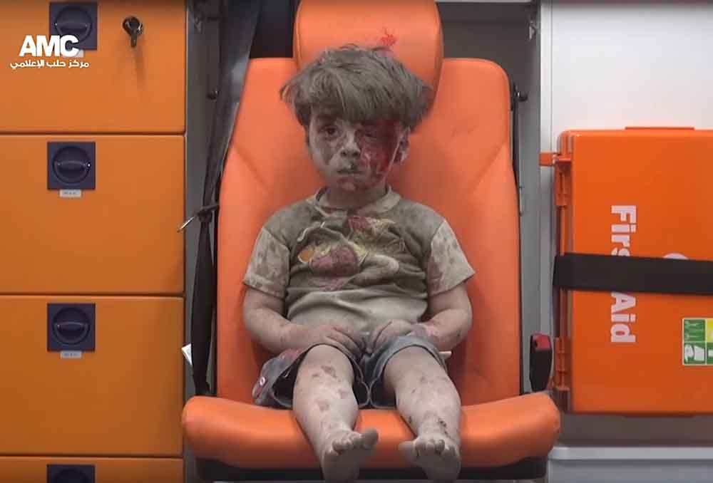 A screenshot from a handout video made available on Aug. 18, 2016 by Syrian activist group Aleppo Media Center (AMC) shows a boy with a bloodied face sitting in an ambulance after a house was destroyed in an airstrike on Aug. 17, 2016 in Aleppo, Syria. Eight people, including five children, are said to have been killed in the attack. (Aleppo Media Center/DPA/ZUMA Press)